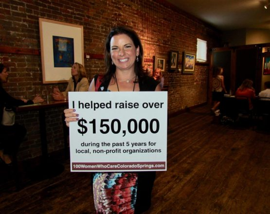 woman holding sign of amount raised for 100 women who care colorado springs